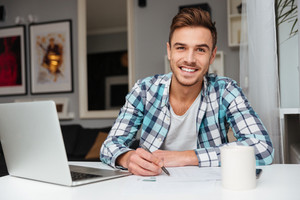 Image of joyful bristle man dressed in shirt in a cage print sitting in home and using laptop computer while writing notes for analyzing home finances.