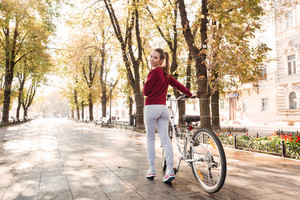 Image of joyful lady dressed in sweater walking with her bicycle outdoors. Look at camera.
