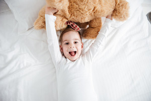 Image of joyful little boy lies on bed at home holding teddy bear. Look at camera.