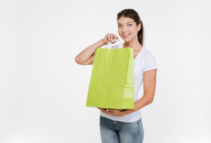 Image of joyful woman holding purchasing after shopping and showing it to camera. Isolated over white background.
