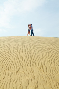 Image of kissing couple during vacation on sandy beach