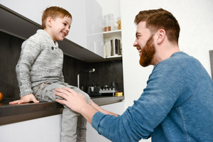 Image of laughing bearded father dressed in blue sweater playing with his little cute son in kitchen