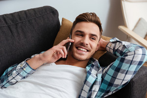 Image of laughing bristle man dressed in shirt in a cage print lies on sofa in home and talking by his phone. Looking aside.