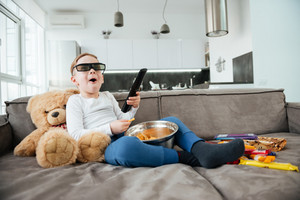 Image of little boy on sofa with teddy bear at home watching TV with 3d glasses while eating chips. Holding remote control.
