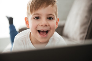 Image of little cheerful boy using laptop computer while lies on sofa at home. Look at camera.