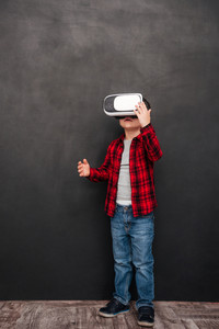 Image of little child wearing virtual reality device over blackboard