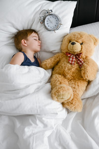Image of little cute boy sleeping with teddy bear in bed near alarm. Eyes closed.