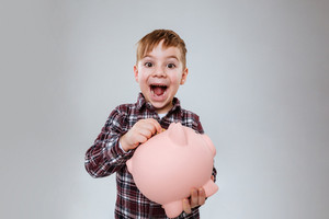 Image of little cute child standing over grey background holding pink pig moneybox. Look at camera.