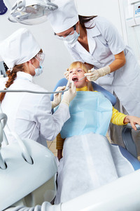 Image of little girl healing her teeth in dentist's office