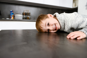 Image of little happy child lies in kitchen table indoors. Look at camera.