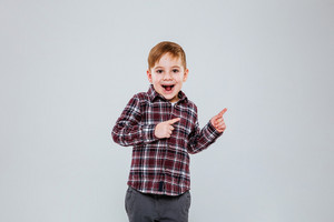 Image of little happy child standing over grey background while pointing. Look at camera.