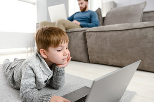 Image of little pretty child using laptop while lies in floor indoors. Look at laptop.