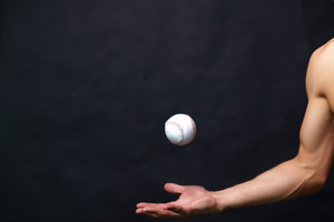 Image of male arm playing with baseball ball over black background
