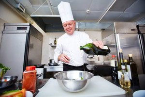 Image of male chef pouring olive oil into bowl in the kitchen