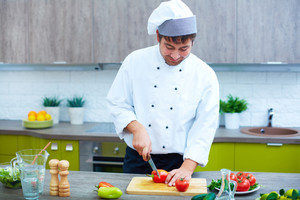 Image of male chef with knife cutting vegs on wooden board