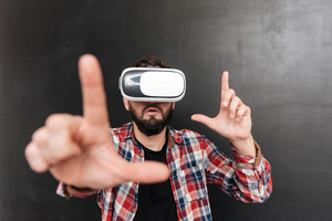 Image of man dressed in shirt in a cage and wearing virtual reality device standing over chalkboard