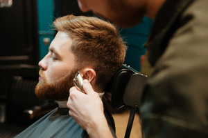 Image of man getting beard haircut by hairdresser while sitting in chair at barbershop.