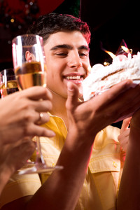 Image of man looking at cake with glasses in human hands near by