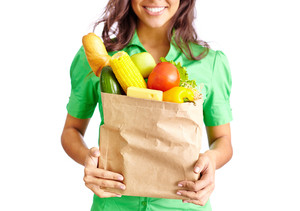 Image of paper packet full of different fruits and vegetables held by smiling female