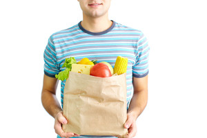 Image of paper packet full of healthy food held by male