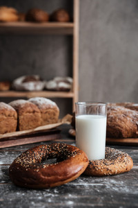 Image of pastries on dark wooden table and bread on background with milk at bakery