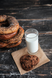 Image of pastries on dark wooden table with milk and cookie at bakery