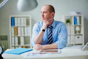 Image of pensive businessman in formalwear working in office