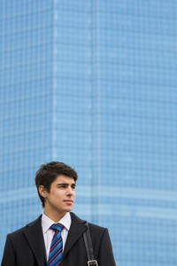 Image of pensive guy looking aside on the background of modern office building