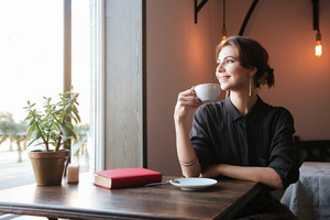 Image of pretty cheerful young woman sitting at the table in cafe and looking aside while drinking coffee.