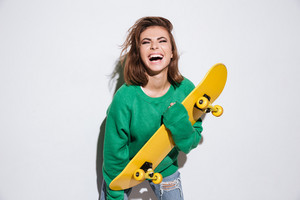 Image of pretty skater lady dressed in green sweater standing isolated over white background with skateboard.