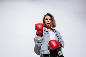 Image of pretty woman boxer dressed in jeans jacket and gloves make boxing exercise isolated over white background