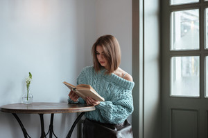 Image of pretty young lady sitting at the table in cafe and reading book.