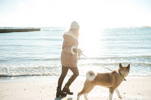 Image of pretty young lady walks in winter beach with dog on a leash.