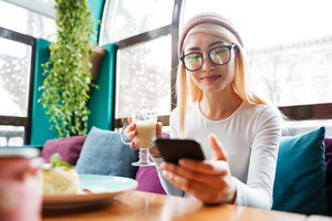 Image of pretty young lady wearing hat and glasses using cellphone while sitting in cafe.