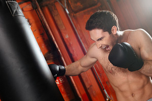 Image of screaming strong boxer training in a gym with punchbag. Looking at punchbag.