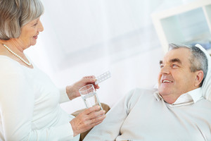 Image of senior female offering her sick husband to take pill