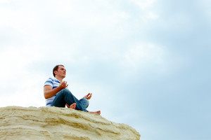 Image of serene man meditating on cliff