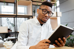 Image of serious african student wearing eyeglasses in library learning education material with books.