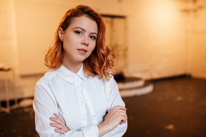 Image of serious redhead young woman dressed in white shirt looking at camera with arms crossed.