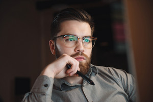 Image of serious web designer dressed in shirt and wearing eyeglasses working late at night and looking at computer.