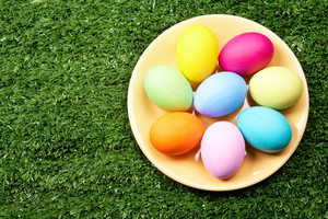 Image of several colored eggs placed on plate over grassland