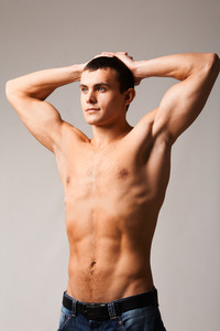 Image of shirtless man in jeans looking forwards with his hands on top of head