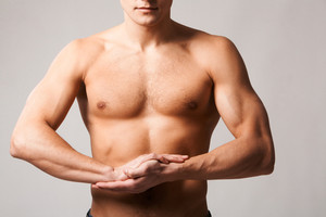Image of shirtless man keeping his arms by chest