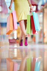 Image of shopaholic with shopping bags walking down mall