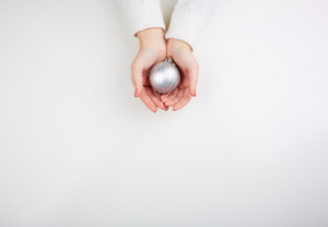 Image of silver decorative toy ball on female hands in isolation