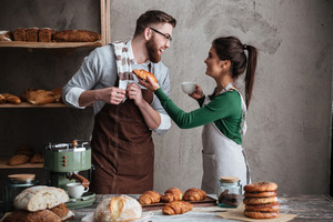 Image of smiling loving couple bakers standing near bread and croissants drinking coffee. Looking aside.