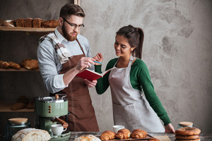 Image of smiling loving couple bakers standing near bread and croissants. Looking at notebook.