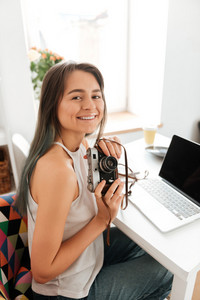 Image of smiling young lady sitting on the chair in the house while holding camera. Look at camera.