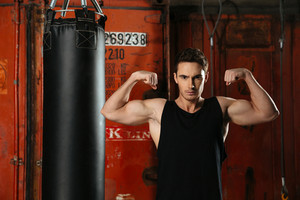 Image of strong boxer standing in a gym near punch bag and showing his biceps. Looking at camera.