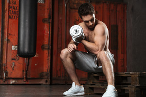 Image of strong man make sport exercises with sport ecquipment in a gym. Looking at biceps.